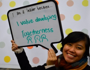 "Student holds a sign that reads ""I am a leader because... I value developing togetherness"""
