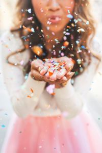 Girl blowing a pile of confetti